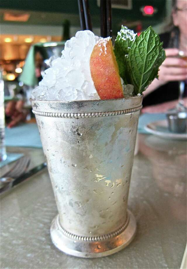 SOUTHERN SIP: Celeb chef Bryan Caswell's Gulf-seafood-savvy Reef restaurant in Midtown now offers a seasonal Peach Julep, made with a peach whiskey from Whitmeyer's Distilling in Houston. Served in a traditional silver julep tumbler, it arrives heaped with crushed ice that melts into the strong drink as you sip it with a straw, all topped off with a peach segment and fresh mint leaves. 2600 Travis, 713-526-8282, reefhouston.com. Photo: Alison Cook