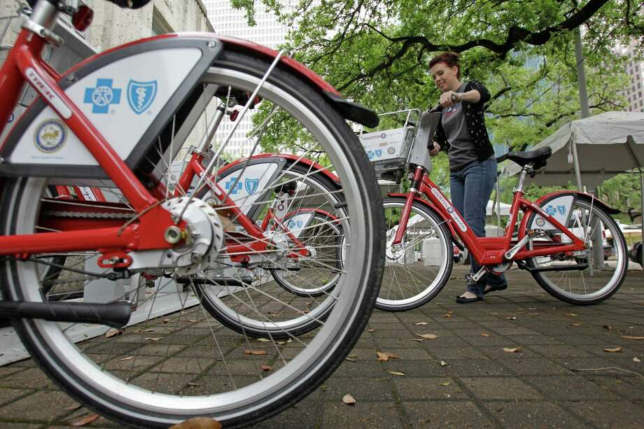 Houston B-Cycle employee Paige Cline removes a bike from a station outside City Hall  on April 3, 2013. After a three-phase expansion planned for 2016, the system will grow to 800 bicycles across 100 stations around Houston. ( Melissa Phillip / Houston Chronicle ) Photo: Melissa Phillip, Staff / © 2013  Houston Chronicle