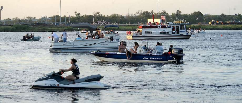 Boats and jetskis enjoy the Neches River while waiting for the 2009 fireworks display to begin at Riverfront Park in Beaumont. Jefferson County commissioners were expected to rule Monday  on whether there will be a full or partial ban on Fourth of July fireworks in the county. Enterprise file photo