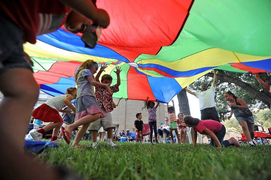 Children run under a parachute during the Fourth of July celebration in down town Beaumont.  Guiseppe Barranco/The Enterprise