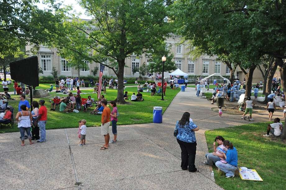 People gather in between the Julie Rogers Theatre and the Beaumont Public Library for the Fourth of July fireworks show. With Riverfront Park under construction, Independence Day festivities were relocated.   Guiseppe Barranco/The Enterprise