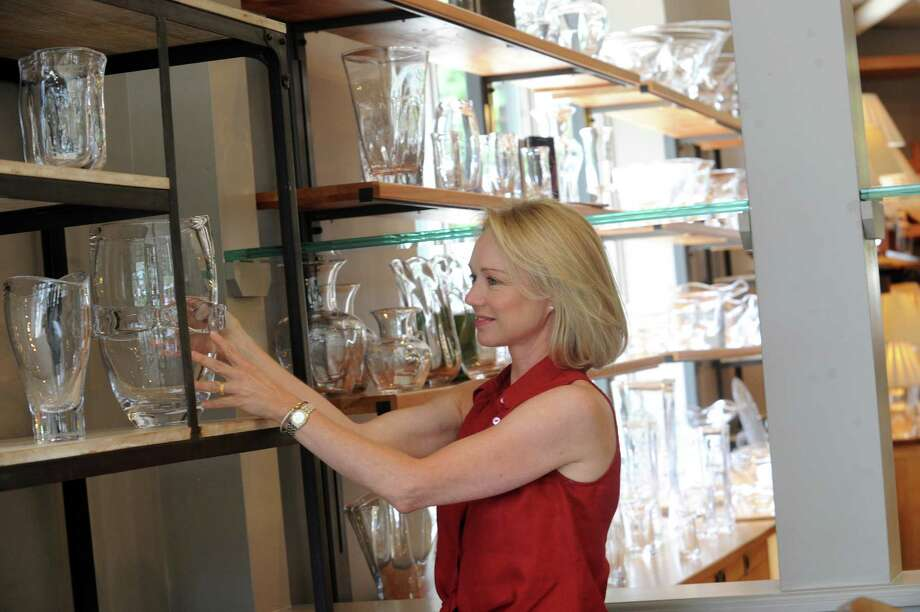 Lea Anne Miller places a vase from Simon Pearce, in Greenwich, Conn., Wednesday, July 3, 2013. Miller, a Greenwich-based event planner, was the first in a proposed series of local designers to showcase their work at Simon Pearce's retail store. Photo: Helen Neafsey / Greenwich Time