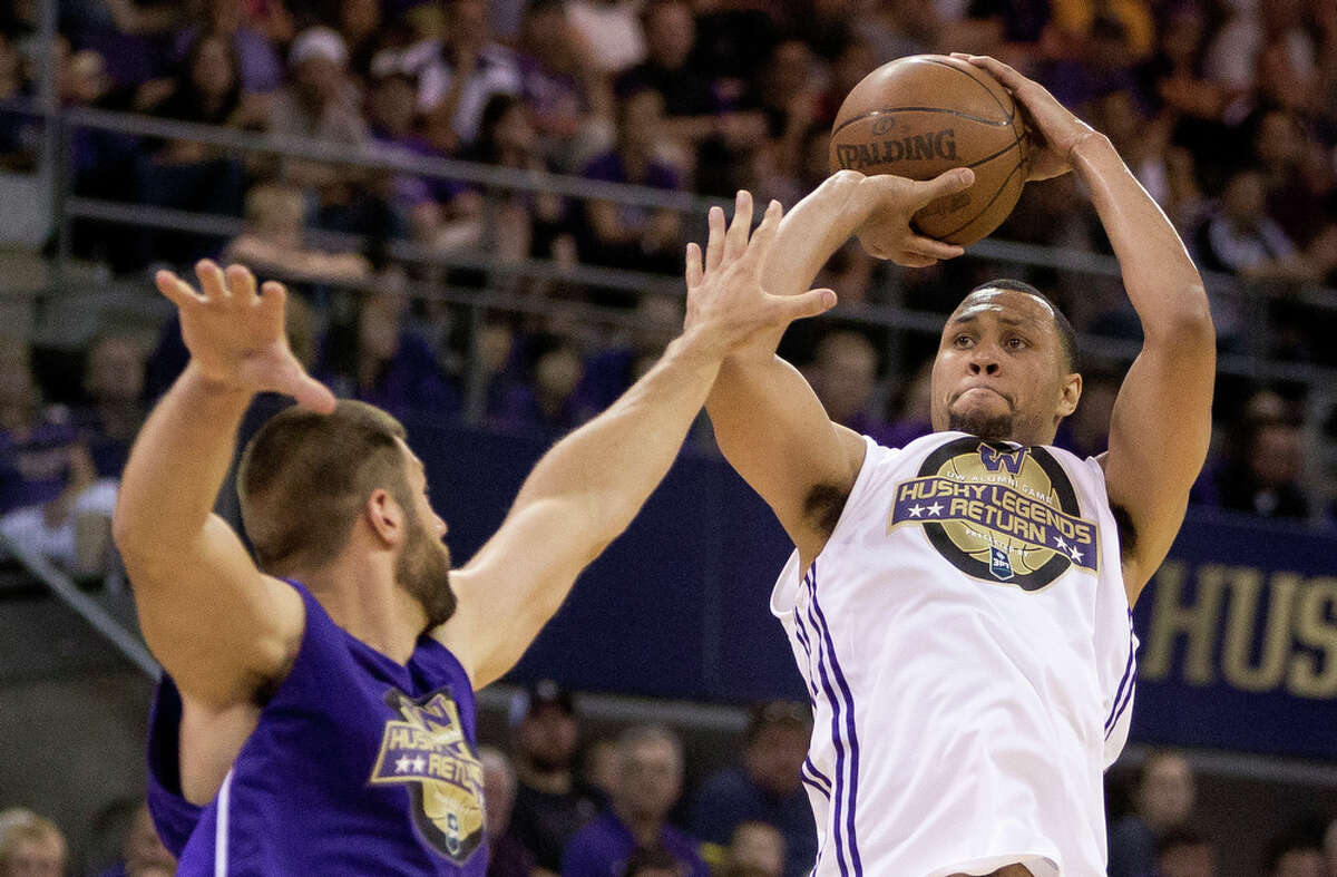 Brandon Roy, right, takes a jump shot over the competition during the University of Washington Alumni Game Sunday, June 23, 2013, in the Alaska Airlines Arena at the University of Washington in Seattle, Wash.