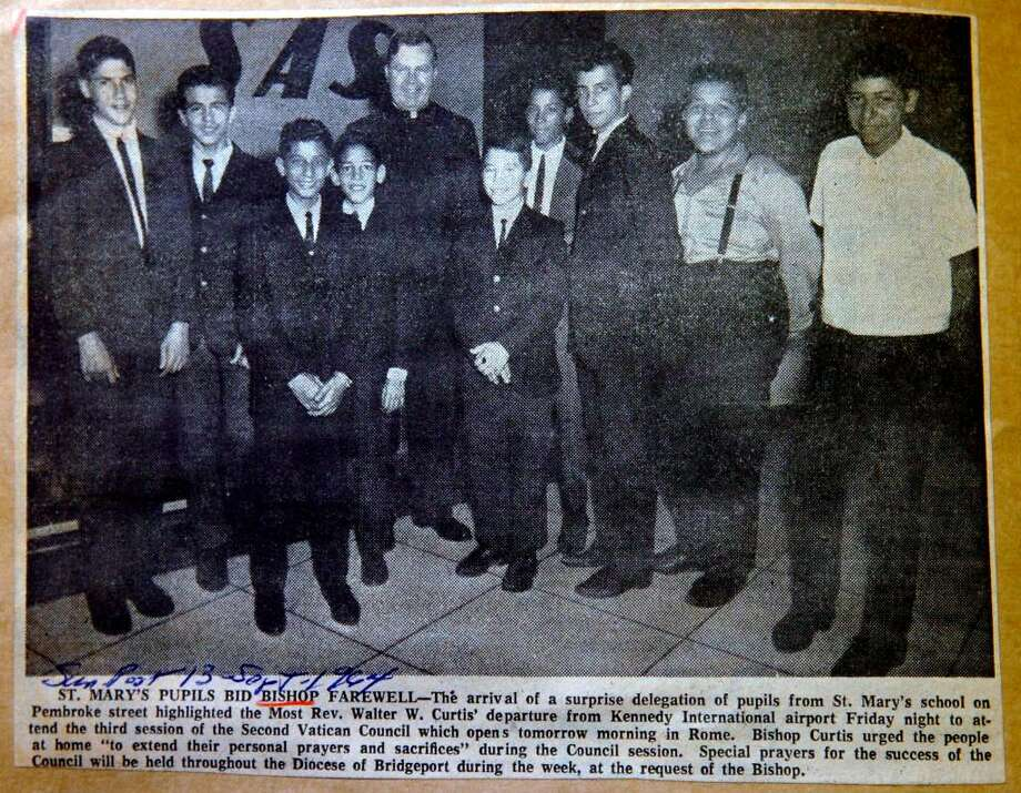 A newspaper clipping in the files of the Bridgeport Historic Collections from the Sunday, Sept. 13th, 1964 Bridgeport Post. The photograph shows Bishop Walter W. Curtis with pupils from the St. Mary's school. Angel Baez, then 14, stands second from the right, wearing suspenders. Now 59 and in poor health, Baez is looking for the names of his fellow classmates who were in a photo. Photo: Contributed Photo / Connecticut Post Contributed