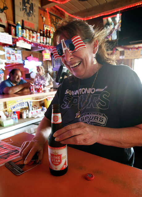 Bartender Sue Miller serves up a customer at the Texas Ice House on July 3, 2013. Photo: Tom Reel, San Antonio Express-News