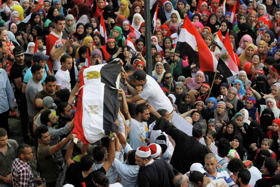 Opponents of Egypt's Islamist President Mohammed Morsi prepare to pray funeral prayers, for Egyptians who were killed during clashes between supporters and opponents of President Morsi, in front of a symbolic coffin covered by the national flag in Tahrir Square in Cairo, Egypt, Wednesday, July 3, 2013. Army troops backed by armor and including commandos have deployed across much of the Egyptian capital, near protest sites and at key facilities and major intersections. The deployment is part of a bid by the military to tighten its control of key institutions Wednesday, slapping a travel ban on embattled president Mohammed Morsi and top allies in preparation for an almost certain push to remove the Islamist president with the expiration of an afternoon deadline. Photo: AP