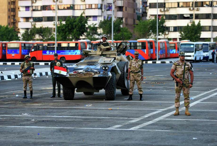 Egyptian army soldiers stand guard in Nasser City, Cairo, Egypt, Wednesday, July 3, 2013. Army troops backed by armor and including commandos have deployed across much of the Egyptian capital, near protest sites and at key facilities and major intersections. The deployment is part of a bid by the military to tighten its control of key institutions Wednesday, slapping a travel ban on embattled president Mohammed Morsi and top allies in preparation for an almost certain push to remove the Islamist president with the expiration of an afternoon deadline. Photo: Hassan Ammar