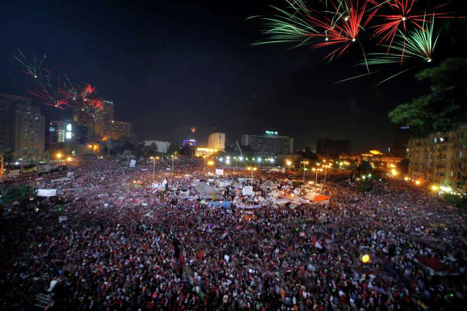 Fireworks light the sky as opponents of Egypt's Islamist President Mohammed Morsi celebrate in Tahrir Square in Cairo, Egypt, Wednesday, July 3, 2013. Army troops backed by armor and including commandos have deployed across much of the Egyptian capital, near protest sites and at key facilities and major intersections. The deployment is part of a bid by the military to tighten its control of key institutions Wednesday, slapping a travel ban on embattled president Mohammed Morsi and top allies in preparation for an almost certain push to remove the Islamist president with the expiration of an afternoon deadline. Photo: Amr Nabil