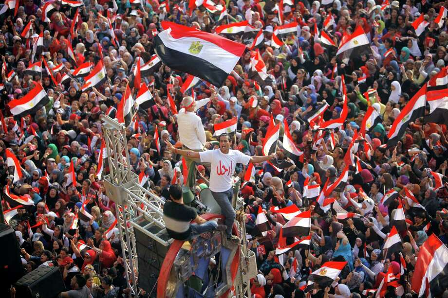 "Opponents  of Egypt's Islamist President Mohammed Morsi shout slogans and wave a national flags in Tahrir Square in Cairo, Egypt, Wednesday, July 3, 2013.  Arabic reads, "" leave."" The deadline on the military's ultimatum to President Mohammed Morsi has expired, with 48 hours passing since the time it was issued. Giant cheering crowds of Morsi's opponents have been gathered in Cairo's Tahrir Square and other locations nationwide, waving flags furiously in expection that the military will act to remove the Islamist president after the deadline ends. Photo: Amr Nabil"
