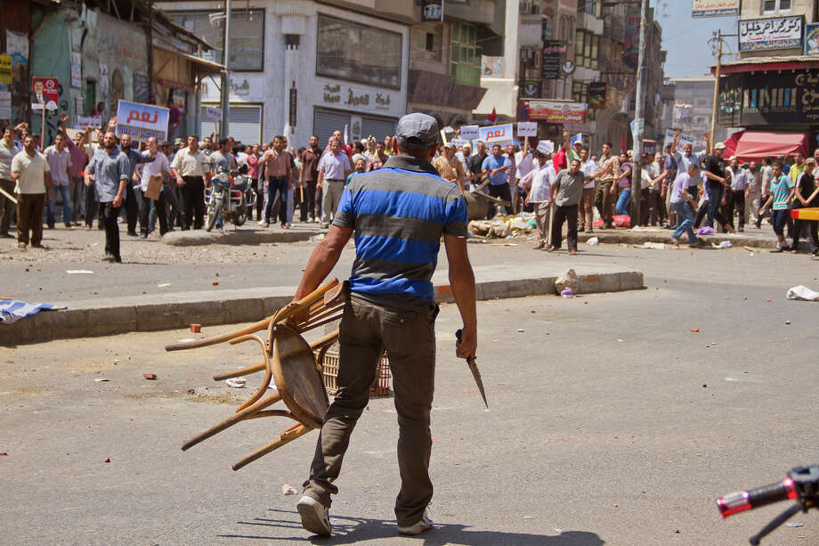 An Egyptian opposition protester holds a chairr and knife during a clash between supporters and opponents of President Mohammed Morsi in downtown Damietta, Egypt, Wednesday, July 3, 2013. he deadline on the military's ultimatum to President Mohammed Morsi has expired, with 48 hours passing since the time it was issued. Giant cheering crowds of Morsi's opponents have been gathered in Cairo's Tahrir Square and other locations nationwide, waving flags furiously in expection that the military will act to remove the Islamist president after the deadline ends. Photo: AP