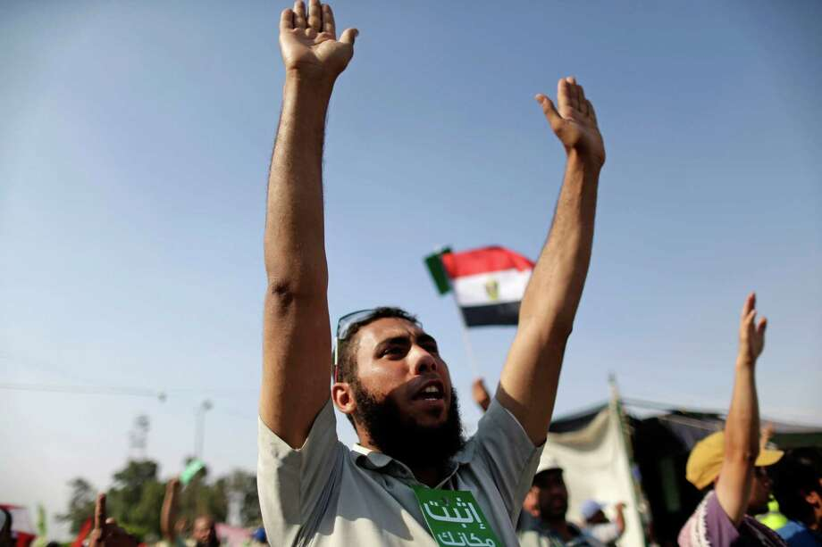 """Supporters of Egypt's Islamist President Mohammed Morsi chant slogans during a rally, in Nasser City, Cairo, Egypt, Wednesday, July 3, 2013. The green card with Arabic reads, """"stay where you are.""""  Egypt's military moved to tighten its control on key institutions Wednesday, even putting officers in the newsroom of state TV, in preparation for an almost certain push to remove the country's Islamist president when an afternoon ultimatum expires. Photo: Hassan Ammar"""