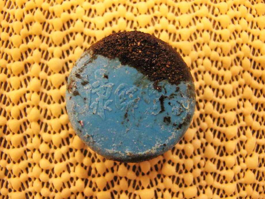 Bottle cap coated with oiled sand still lingering from Exxon Valdez. Photo: Nicholas Mallos/Ocean Conservancy