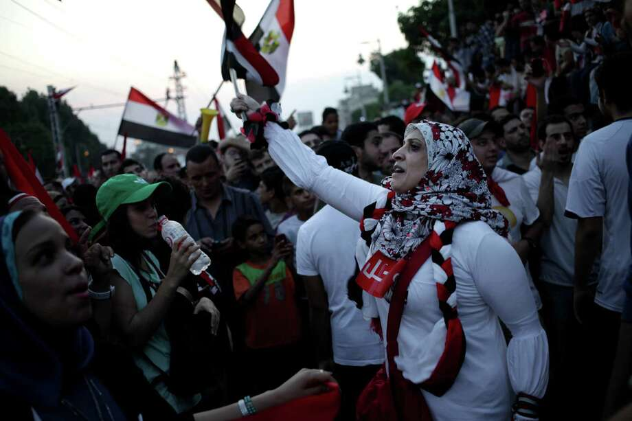 Opponents of Egypt's Islamist President Mohammed Morsi celebrate outside the presidential palace in Cairo, Egypt, Wednesday, July 3, 2013. Army troops backed by armor and including commandos have deployed across much of the Egyptian capital, near protest sites and at key facilities and major intersections. The deployment is part of a bid by the military to tighten its control of key institutions Wednesday, slapping a travel ban on embattled president Mohammed Morsi and top allies in preparation for an almost certain push to remove the Islamist president with the expiration of an afternoon deadline. Photo: Khalil Hamra