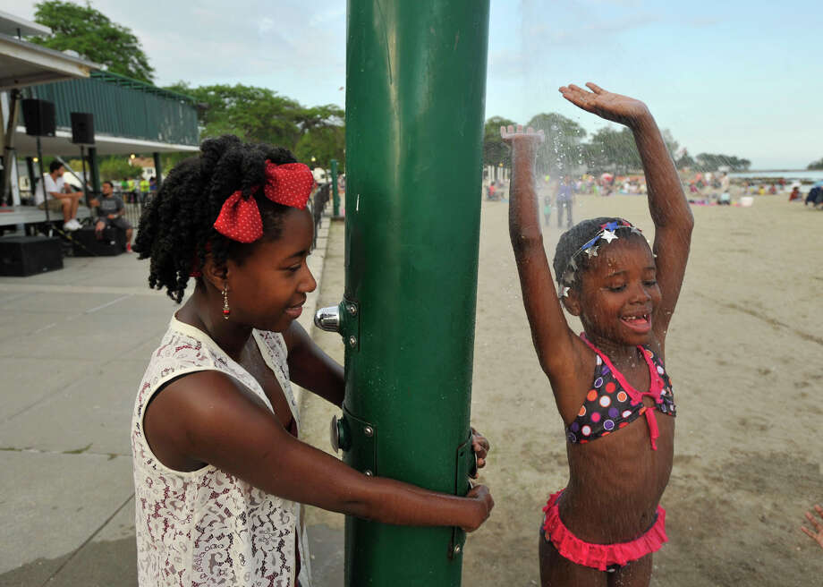 Audrienne Brissett, left, keeps the shower on for her neice Naia Brissett before the fireworks show at Cummings Park beach on Wednesday, July 3, 2013. Photo: Jason Rearick / Stamford Advocate