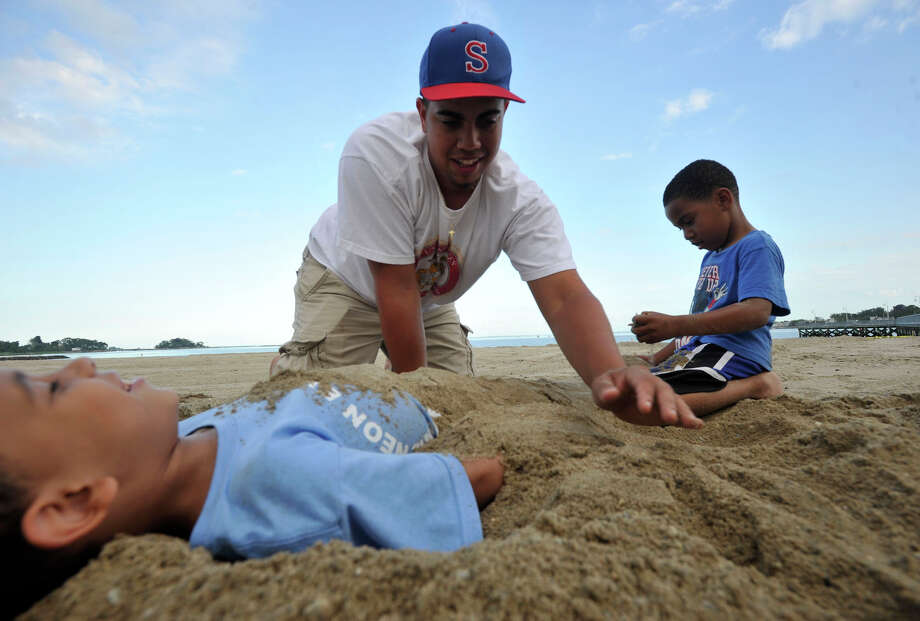 Nelson Terrero, top, burries his cousin, Josiah Crespo, in the sand with the help of his other cousin Kevin Rojas Jr before the fireworks show at Cummings Park beach on Wednesday, July 3, 2013. Photo: Jason Rearick / Stamford Advocate