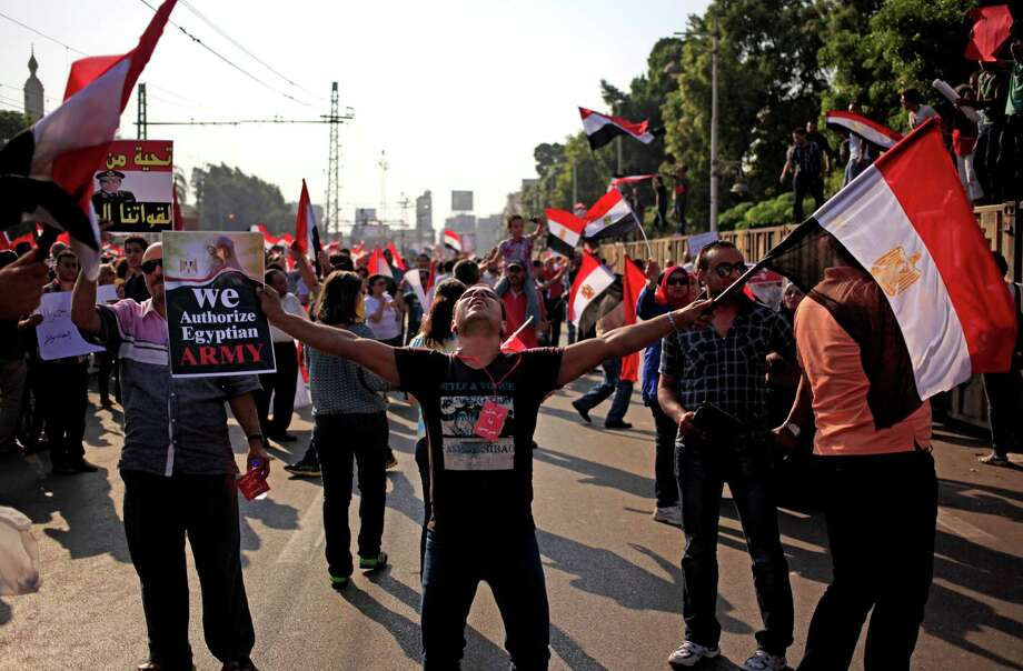Opponents of Egypt's Islamist President Mohammed Morsi wave national flags during a protest outside the presidential palace, in Cairo, Egypt, Wednesday, July 3, 2013. The deadline on the military's ultimatum to President Mohammed Morsi has expired, with 48 hours passing since the time it was issued. Giant cheering crowds of Morsi's opponents have been gathered in Cairo's Tahrir Square and other locations nationwide, waving flags furiously in expection that the military will act to remove the Islamist president after the deadline ends. Photo: Khalil Hamra