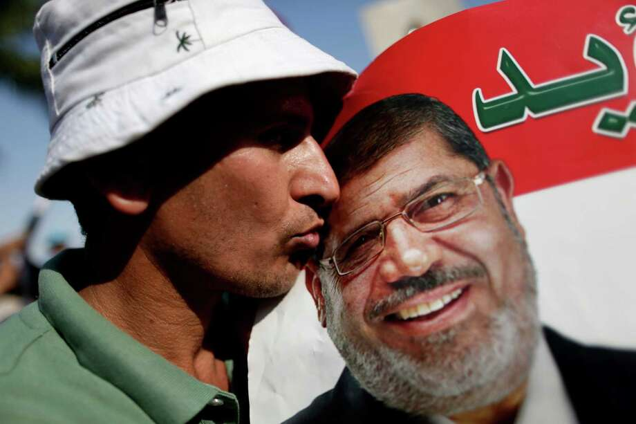 A man kisses a poster with the photograph of Egypt's Islamist President Mohammed Morsi during a rally, in Nasser City, Cairo, Egypt, Wednesday, July 3, 2013.  Egypt's military moved to tighten its control on key institutions Wednesday, even putting officers in the newsroom of state TV, in preparation for an almost certain push to remove the country's Islamist president when an afternoon ultimatum expires. Photo: AP