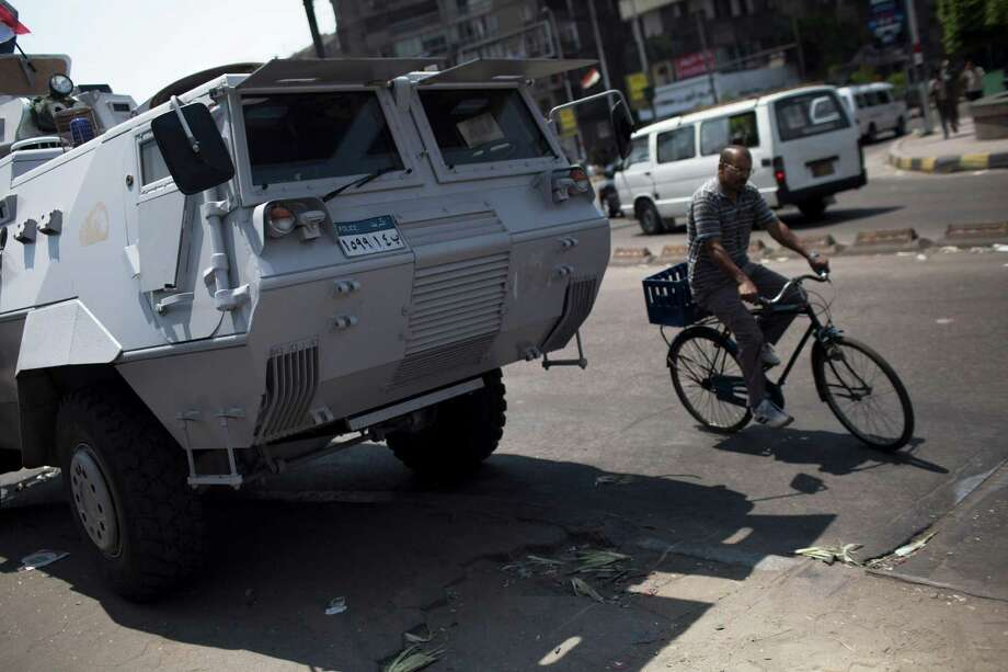 An Egyptian man rides a bicicle past an armored vehicle protecting a bridge between Tahrir Square and Cairo University, where Muslim Brotherhood supporters have gathered, in Giza, Egypt, Wednesday, July 3, 2013.  Egypt's leading democracy advocate Mohamed ElBaradei and top Muslim and Coptic Christian clerics met Wednesday with the army chief to discuss a political road map for Egypt only hours before a military ultimatum to the Islamist president was set to expire. Photo:  Manu Brabo