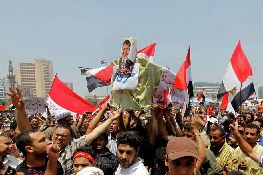 "Opponents of Egypt's Islamist President Mohammed Morsi shout slogans as they carry a symbolic coffin of Morsi during a protest in Tahrir Square in Cairo, Egypt, Wednesday, July 3, 2013. A Defense Ministry official said army chief Gen. Abdel-Fattah el-Sissi is meeting with his top commanders, hours before the military's deadline to the president and opposition to resolve the nation's political crisis is set to expire. Arabic reads, ""Lamb."" Photo: Amr Nabil"