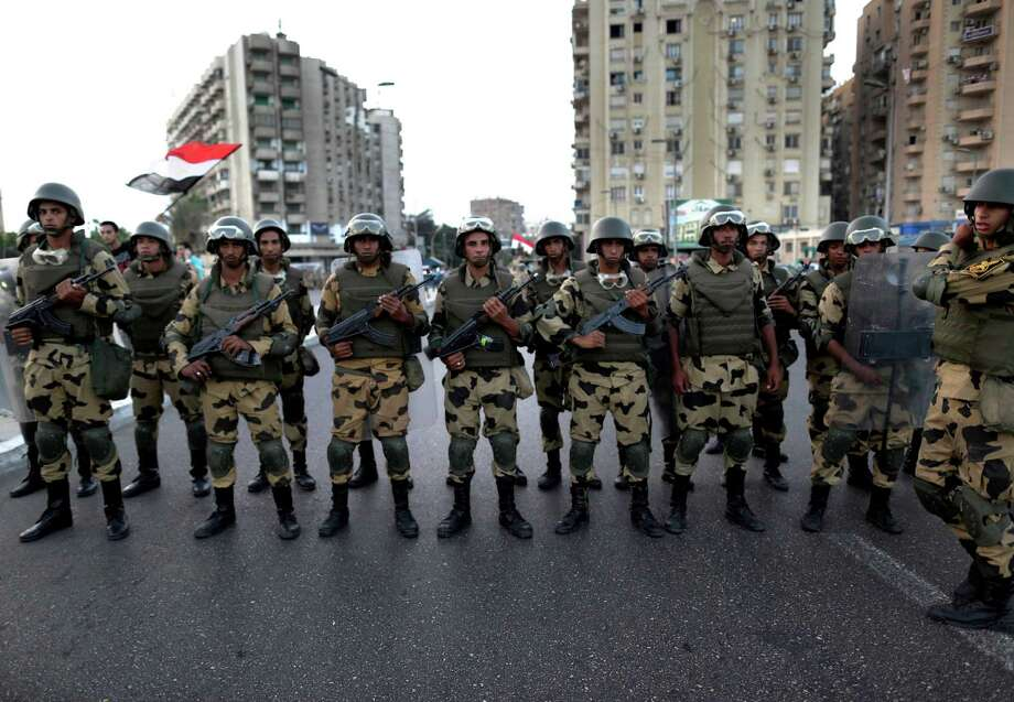 Military special forces surround supporters of Islamist leader Mohammed Morsi in Nasser City, Cairo, Egypt, Wednesday, July 3, 2013. Army troops backed by armor and including commandos have deployed across much of the Egyptian capital, near protest sites and at key facilities and major intersections. The deployment is part of a bid by the military to tighten its control of key institutions Wednesday, slapping a travel ban on embattled president Mohammed Morsi and top allies in preparation for an almost certain push to remove the Islamist president with the expiration of an afternoon deadline. Photo: Hassan Ammar