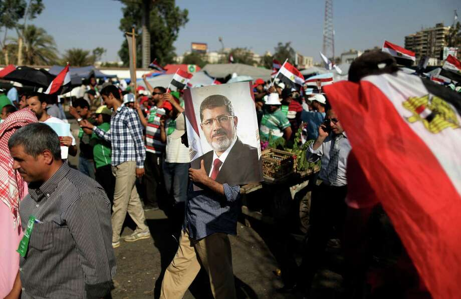 A supporter of Egypt's Islamist President Mohammed Morsi carries a photo of him during a rally, in Nasser City, Cairo, Egypt, Wednesday, July 3, 2013. Airport officials say a travel ban has been issued against the embattled president and the leader of the Muslim Brotherhood. The officials said Wednesday that the travel ban on Morsi has to do with his escape from prison with more than 30 other Muslim Brotherhood during the 2011 uprising against autocrat Hosni Mubarak. Photo: Hassan Ammar