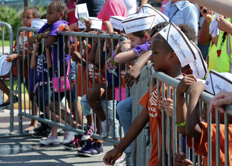 Amont Robinson, 7, moves his arm out past the barricade as he watches as the elephants eat their ice-cold treats. Photo: JERRY LARA, San Antonio Express-News / © 2013 San Antonio Express-News