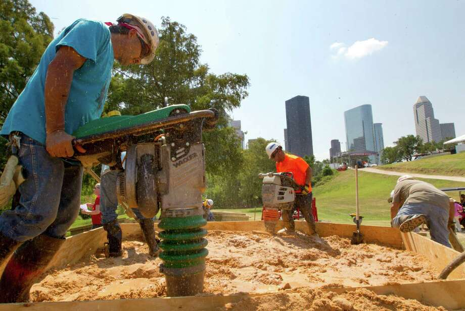 A team works to finish a sandcastle in preparation for the Freedom Over Texas event at Eleanor Tinsley Park, Wednesday, July 3, 2013, in Houston. Designers and artists from Gensler and Harvey will build the sandcastle, and it will serves as a tribute to victims of the tragedies in Boston, Mass., Newtown, Conn., and West, Texas. Photo: Cody Duty, Houston Chronicle / © 2013 Houston Chronicle