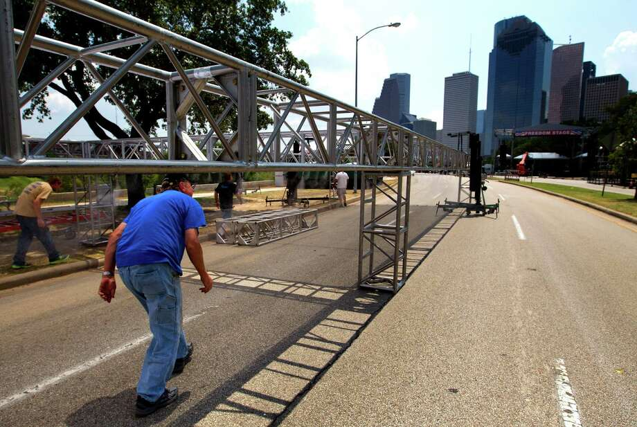 A crew checks the misters hanging from The Cool Zone in preparation for the Freedom Over Texas event at Eleanor Tinsley Park, Wednesday, July 3, 2013, in Houston. The misters will help to cool off attendees during the heat of the event. Photo: Cody Duty, Houston Chronicle / © 2013 Houston Chronicle