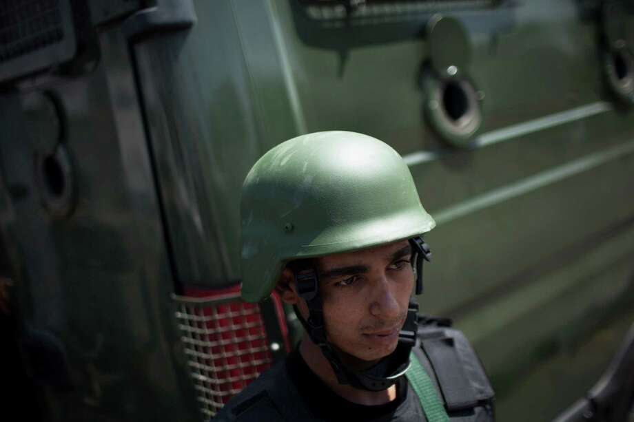 A member of Egyptian police special forces stands guard beside an armored vehicle, protecting a bridge between Tahrir Square and Cairo University, where Muslim Brotherhood supporters have gathered, in Giza, Egypt, Wednesday, July 3, 2013.  Egypt's leading democracy advocate Mohamed ElBaradei and top Muslim and Coptic Christian clerics met Wednesday with the army chief to discuss a political road map for Egypt only hours before a military ultimatum to the Islamist president was set to expire. Photo:  Manu Brabo