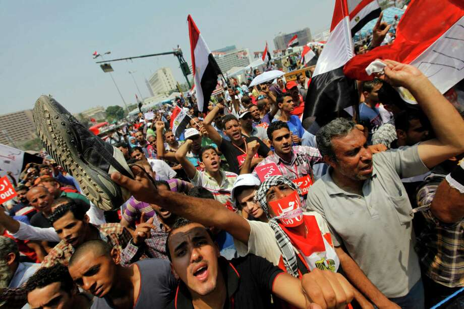 "Opponents of Egypt's Islamist President Mohammed Morsi shout slogans during a protest in Tahrir Square in Cairo, Egypt, Wednesday, July 3, 2013. A Defense Ministry official said army chief Gen. Abdel-Fattah el-Sissi is meeting with his top commanders, hours before the military's deadline to the president and opposition to resolve the nation's political crisis is set to expire. Arabic reads, ""Leave."" Photo: Amr Nabil"