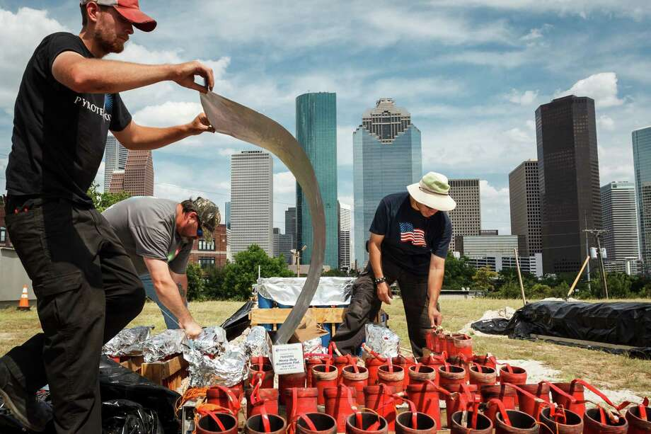 Adam Nickerson, left to right, C.W. McGee and Larry Sanchez place foil over the top of 3in. mortar tubes while preparing fireworks for the Freedom Over Texas: Houston's Official 4th of July Celebration at Eleanor Tinsley Park, Monday, July 1, 2013, in Houston. Photo: Michael Paulsen, Houston Chronicle / © 2013 Houston Chronicle