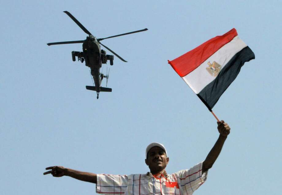 An military helicopter flies over an opponent if Egyptian Islamist President Mohammed Morsi as he waves a national flag, in Tahrir Square in Cairo, Egypt, Tuesday, July 2, 2013. With a military deadline for intervention ticking down, protesters seeking the ouster of Egypt's Islamist president sought Tuesday to push the embattled leader further toward the edge with another massive display of people power. Photo: AP
