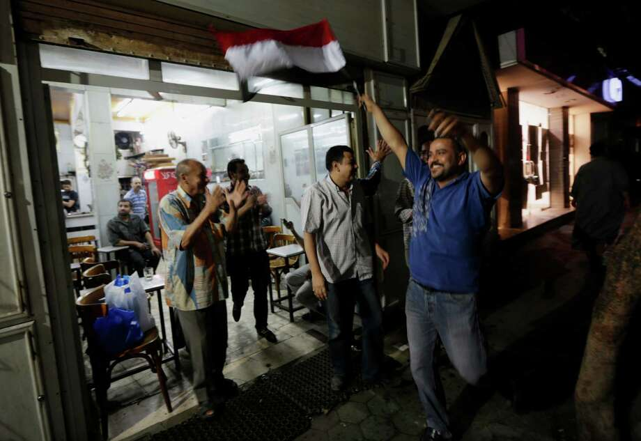 Egyptians celebrate at a tea house at Defense Minister Gen. Abdel-Fattah el-Sissi's announcement in Cairo's Zamalek district Wednesday, July 3, 2013. Egypt's military has suspended the Islamist-backed constitution and called early elections. The military also announced that embattled President Mohammed Morsi will be replaced.Cheers erupted among millions of protesters nationwide who were demanding Morsi's ouster. Photo: Hiro Komae