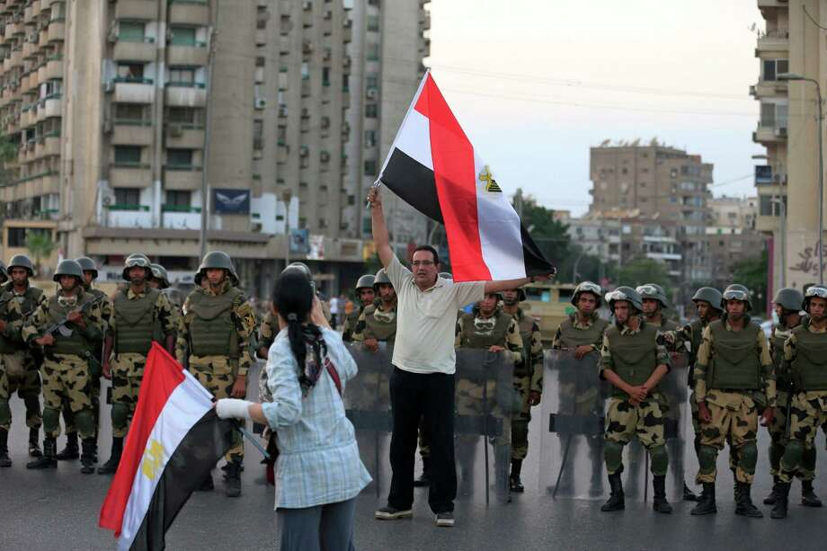 An Egyptian man holds a national flag as military special forces surround supporters of Islamist leader Mohammed Morsi in Nasser City, Cairo, Egypt, Wednesday, July 3, 2013. Army troops backed by armor and including commandos have deployed across much of the Egyptian capital, near protest sites and at key facilities and major intersections. The deployment is part of a bid by the military to tighten its control of key institutions Wednesday, slapping a travel ban on embattled president Mohammed Morsi and top allies in preparation for an almost certain push to remove the Islamist president with the expiration of an afternoon deadline. Photo: Hassan Ammar