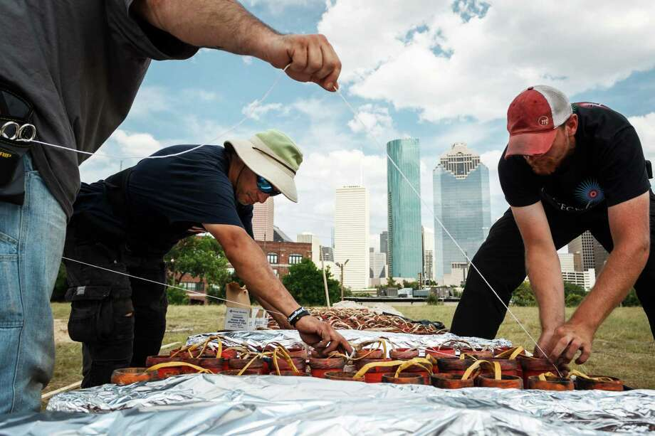 Larry Sanchez, left to right, C.W. McGee and Adam Nickerson place foil over the top of 3in. mortar tubes while preparing fireworks for the Freedom Over Texas: Houston's Official 4th of July Celebration at Eleanor Tinsley Park, Monday, July 1, 2013, in Houston. Photo: Michael Paulsen, Houston Chronicle / © 2013 Houston Chronicle