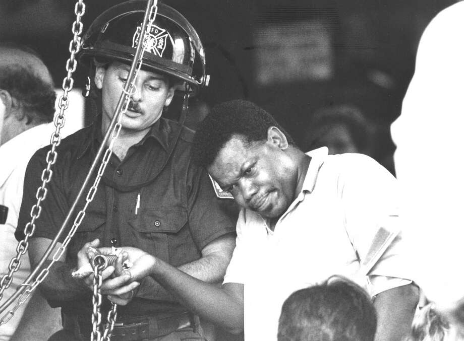 Daniel Clement grimaces on July 13, 1988, as firefighter James Romaniello slowly works to free Clement's thumb from a chain hoist in which it was caught. Paramedics and fire personnel successfully freed him from the machine at Baldwin Technology on Lincoln Avenue. Photo: Advocate