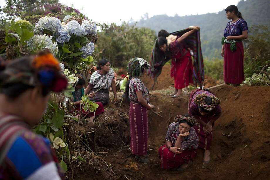 Jacinta Cruz, above, sheds a tear as her mother's remains are exhumed, after three decades, from a clandestine grave, right, near Ixtupil, Guatemala. Photo: Rodrigo Abd, Associated Press