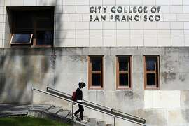 Claudeen Narnac walks down the steps in front of a City College of San Francisco sign which lost its accreditation effective on July 31, 2014 in San Francisco, Calif. on July 3, 2013
