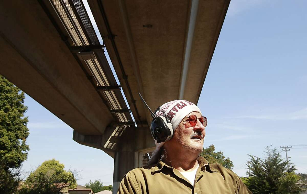 Jim Kart, on Wednesday July 3, 2013, walks the trail under the BART tracks in El Cerrito, Calif. Kart says that the trains sometimes would interfere with his radio reception but during the BART strike with little to no train traffic he can listen much clearer. The BART strike into it's third day is bringing relief to some homeowners that live near the BART trains rushing through the Bay Area, a silence has come about with little to no train traffic moving through their neighborhoods.
