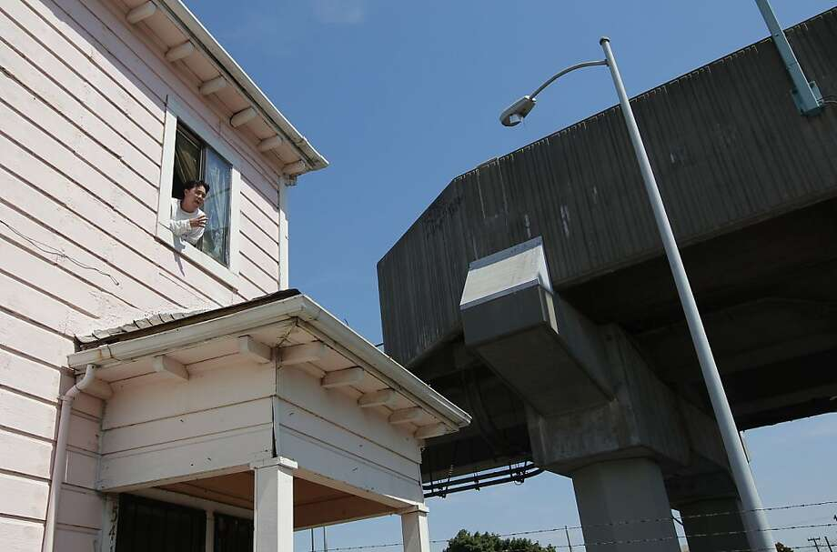 Daniel Villanueva leans out of the window of his room near the West Oakland BART Station platform, no earplugs necessary. Photo: Michael Macor, The Chronicle