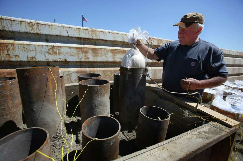 Bob Gobet, co-owner of Western Display Fireworks, loads a 10-inch shell into a tube as workers prepare fireworks on a barge on Seattle's Lake Union. The fireworks will light up the sky for the Seafair Summer Fourth of July celebration, the largest fireworks show in the Pacific Northwest. Photographed on Wednesday, July 3, 2013. Photo: JOSHUA TRUJILLO, SEATTLEPI.COM