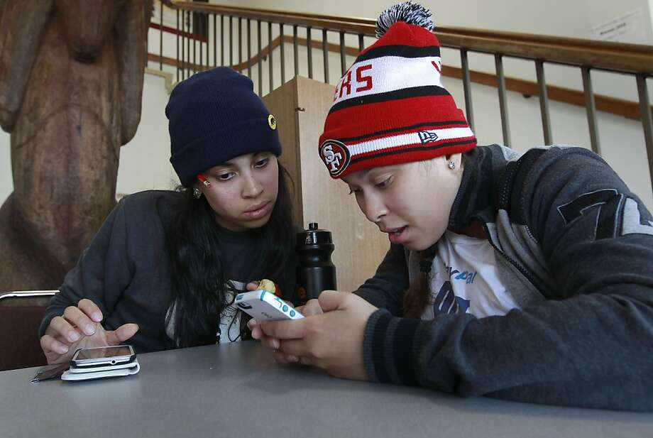 Students Lulu Matute (left) and Gina Rivera read on the school's website about the accrediting commission's decision to revoke City College of San Francisco's accreditation next year. Photo: Michael Macor, The Chronicle