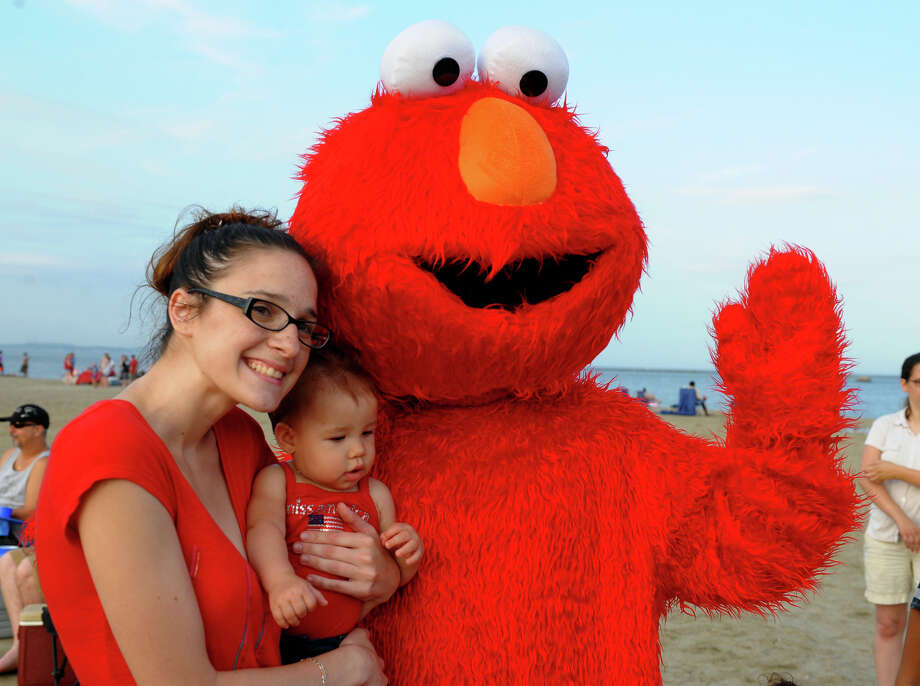 Amanda Traver, of Bridgeport, and her daughter Alivia Garcia,10 months, pose for a photo with Elmo before the start of fireworks at Short Beach in Stratford, Conn. on Wednesday July 3, 2013. Elmo came to the beach as part of entertainment provided by Lynn Lewis and Friends. Photo: Christian Abraham / Connecticut Post