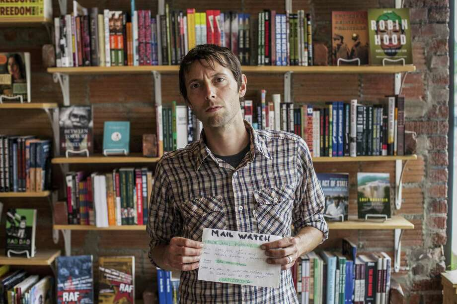 In Buffalo, N.Y., bookstore owner Leslie James Pickering holds a note he found suggesting that his letters, parcels and other mail be monitored. Photo: Brendan Bannon / New York Times