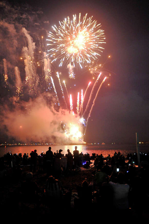 Fireworks go off in Westcott Cove as onlookers watch from Cummings Park beach on Wednesday, July 3, 2013. Photo: Jason Rearick / Stamford Advocate
