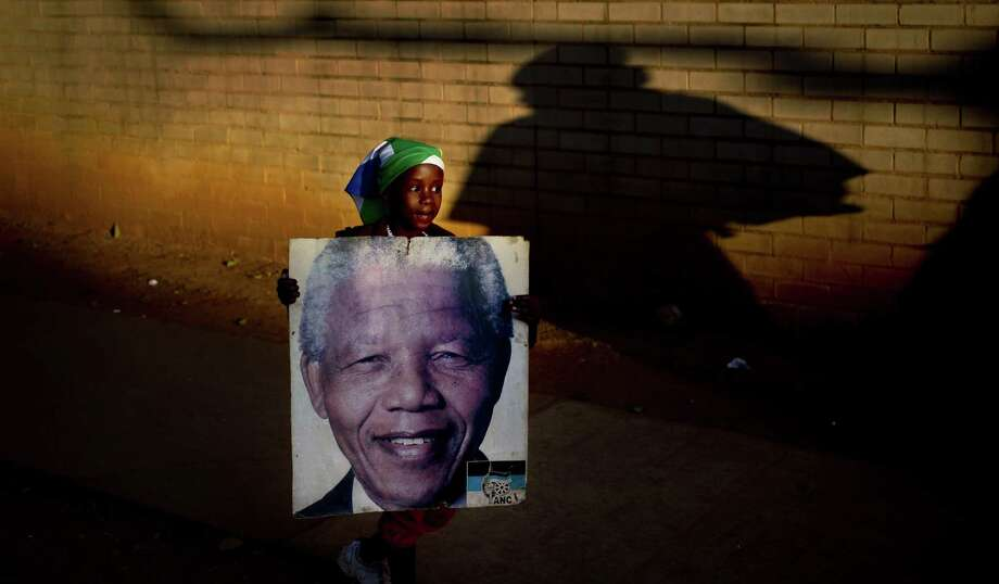 Lehlogonolo Nkosi, 7, holds a portrait of Nelson Mandela in Pretoria near where  the former South African president is being treated at a hospital. Photo: Ben Curtis / Associated Press