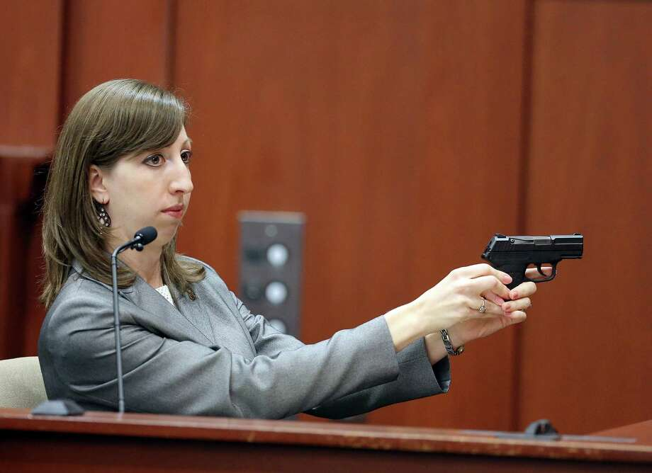 Amy Siewert, a firearms expert with the Florida Department of Law Enforcement, demonstrates George Zimmerman's gun while she faces the jury during the trial Wednesday. Photo: Jacob Langston / Orlando Sentinel
