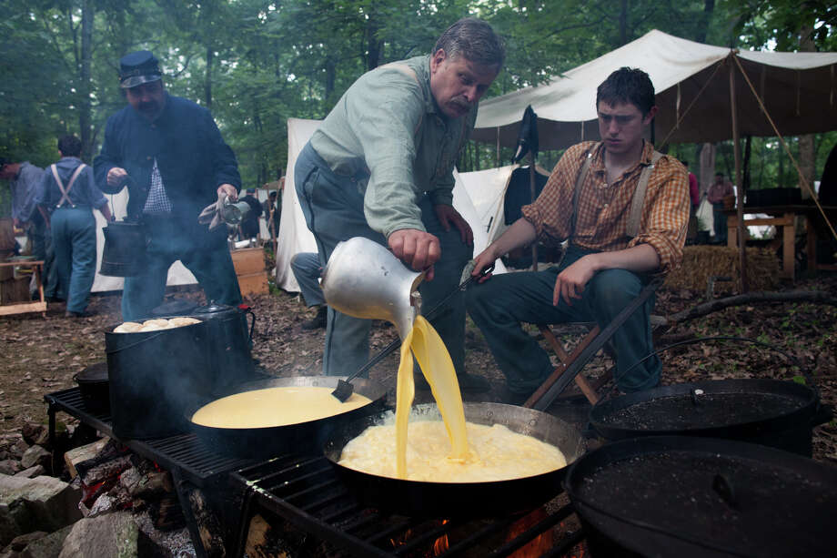 John Newbold, center, and William Krakower, right, prepare a batch of eggs for reenactors participating in ongoing activities in honor of the 150th anniversary of the Battle of Gettysburg, Saturday, June 29, 2013, at Bushey Farm in Gettysburg, Pa. The Union Army stopped a major Confederate advance during a battle fought July 1-3, 1863, often considered the war's major turning point. Photo: Zach Gibson, Associated Press / Richmond Times-Dispatch
