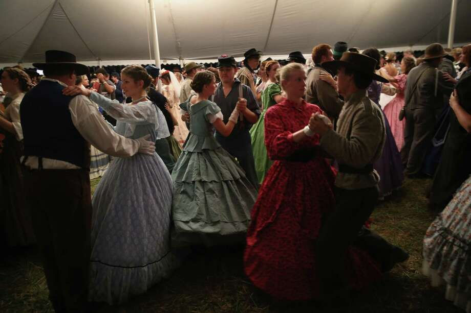 American Civil War re-enactors dance during an evening ball  while taking a break from a three-day Battle of Gettysburg re-enactment on June 29, 2013 in Gettysburg, Pennsylvania. Some 8,000 re-enactors from the Blue Gray Alliance are participating in events marking the 150th anniversary of the July 1-3, 1863 Battle of Gettysburg. General Robert E. Lee's Army of Northern Virginia was defeated on the third day of the battle, considered the turning point in the American Civil War and a watershed moment in the nation's history. Union and Confederate armies suffered a combined total of some 46,000-51,000 casualties over three days, the highest of any battle the four-year war. Photo: John Moore, Getty Images / 2013 Getty Images