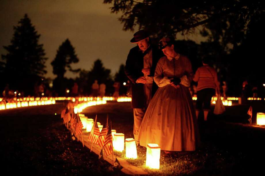 Re-enactors stand near luminaries that mark the graves of Union dead at Soldiers' National Cemetery during ongoing activities commemorating the 150th anniversary of the Battle of Gettysburg, Sunday, June 30, 2013, in Gettysburg, Pa. Photo: Matt Rourke, Associated Press / AP
